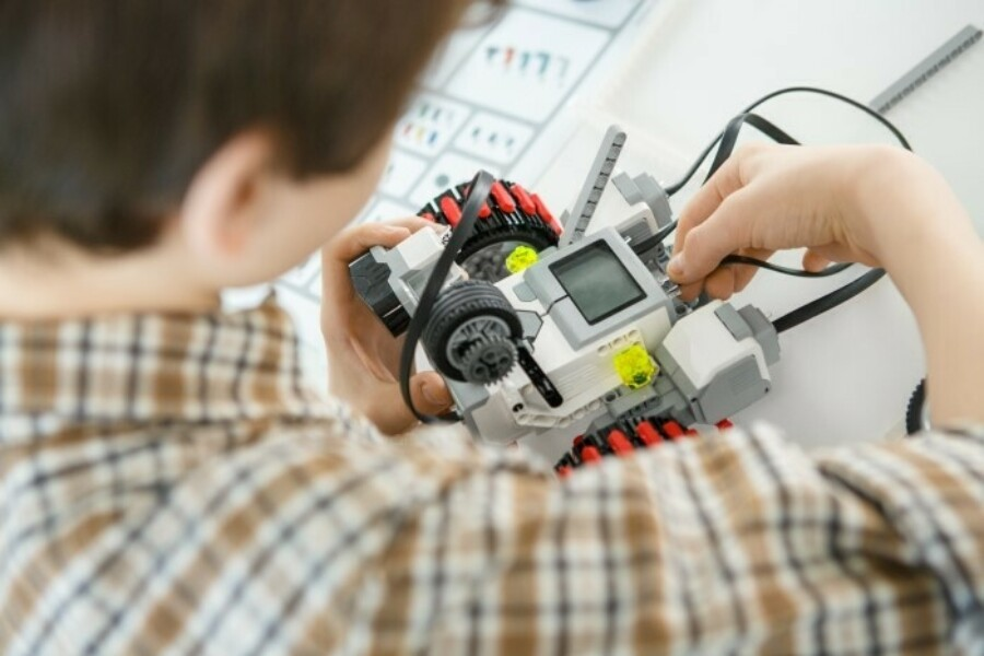 A young boy building robot with blocks and electronics