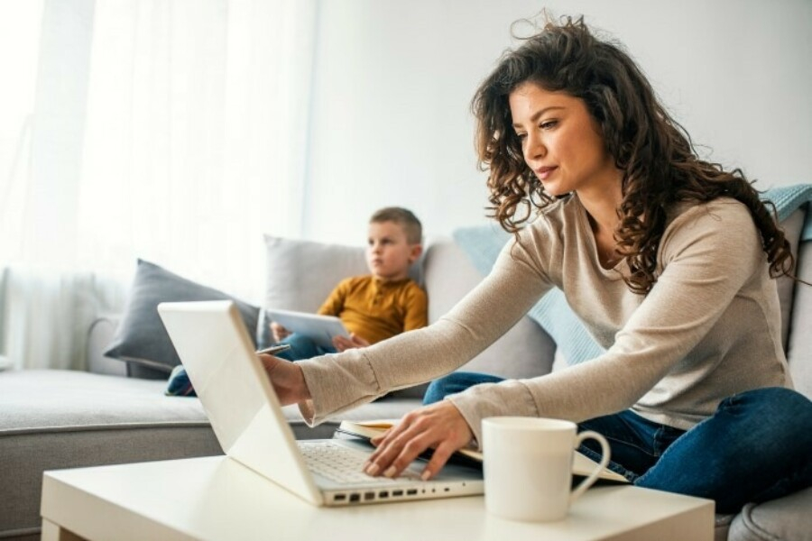 Woman sitting on couch working on laptop with a child in the background