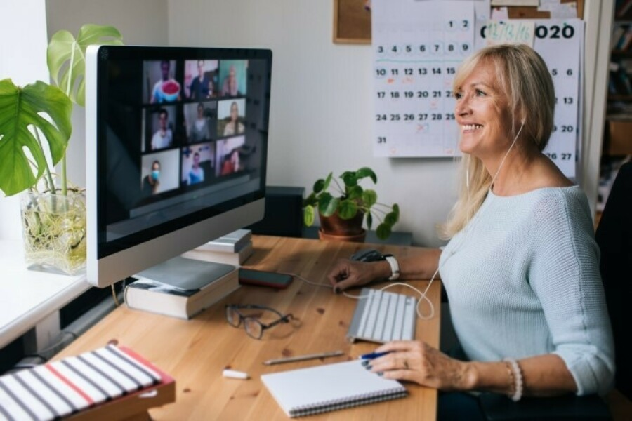 Woman works remotely while on a video conference with team members