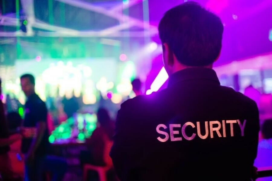 Man standing as security guard at night club.
