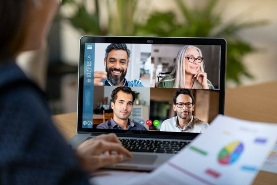 Over a person's shoulder look at computer screen with four people on a video conference
