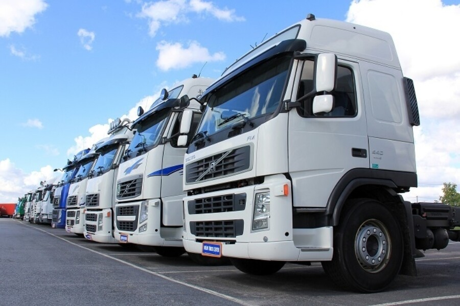 a line of freight trucks in a parking lot