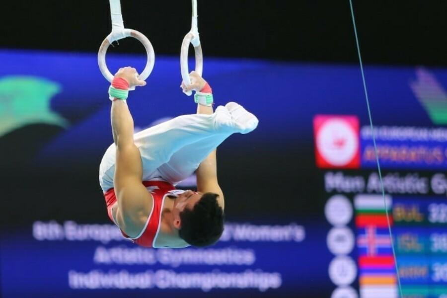 gymnast performing flip on still rings
