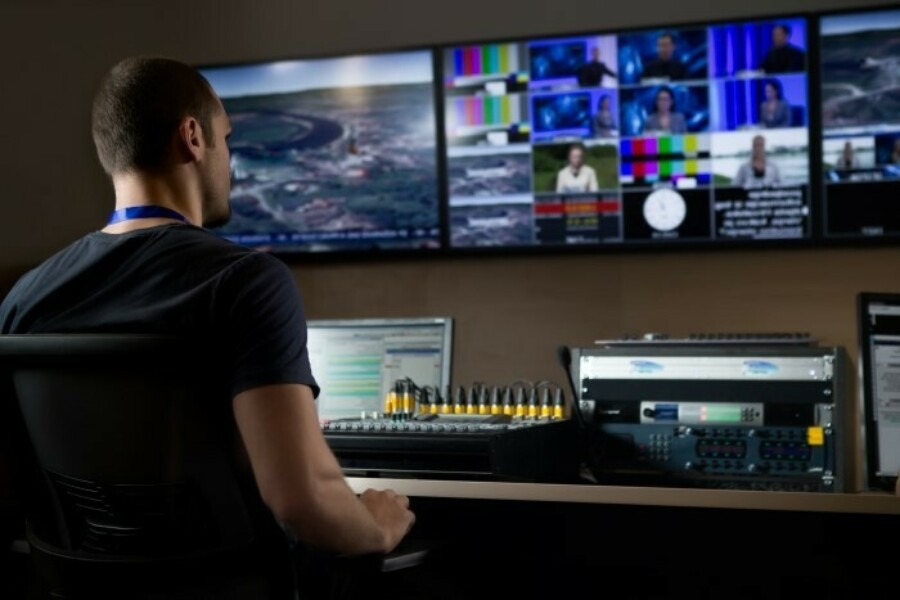man working with technology in a media room