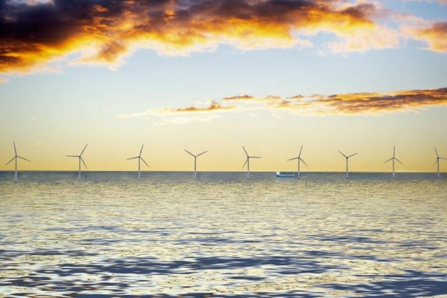 wind farm in the sea at sunset