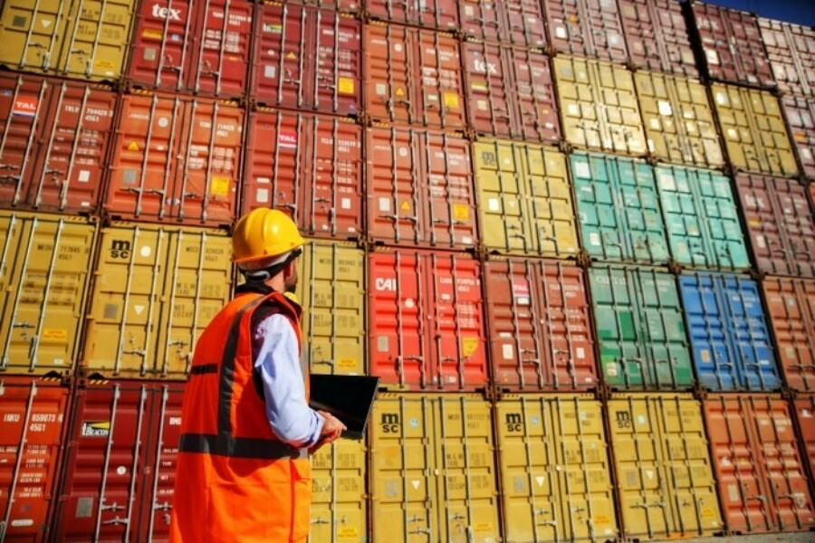 Worker in a hard hat standing by stacks of shipping containers