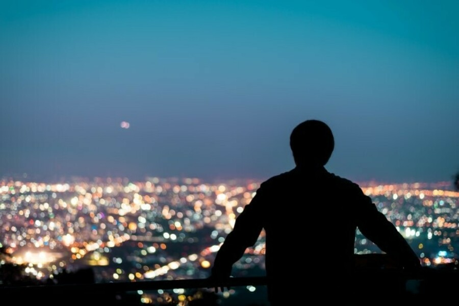 man looking out over city