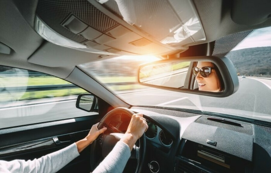 Woman driving a car toward mountains with the sun peaking out in the rearview mirror