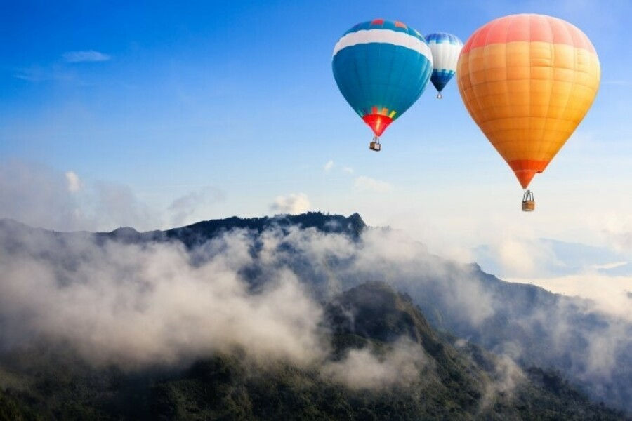 hot air balloons floating in the louds above the mountains