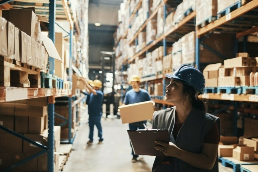Workers in warehouse pulling products off racks