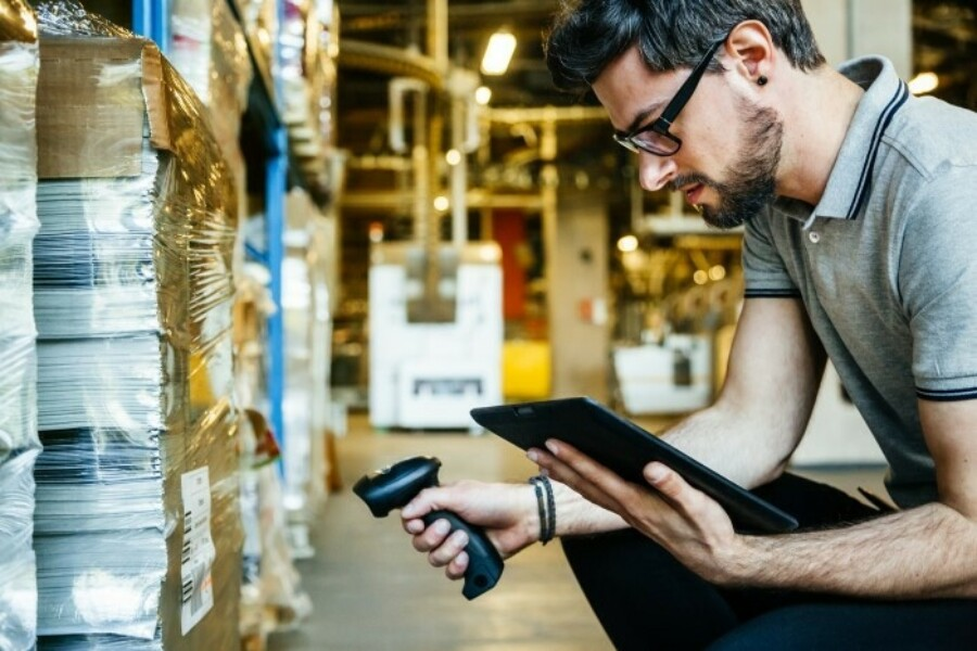 man using tablet and scanner to track goods in a warehouse
