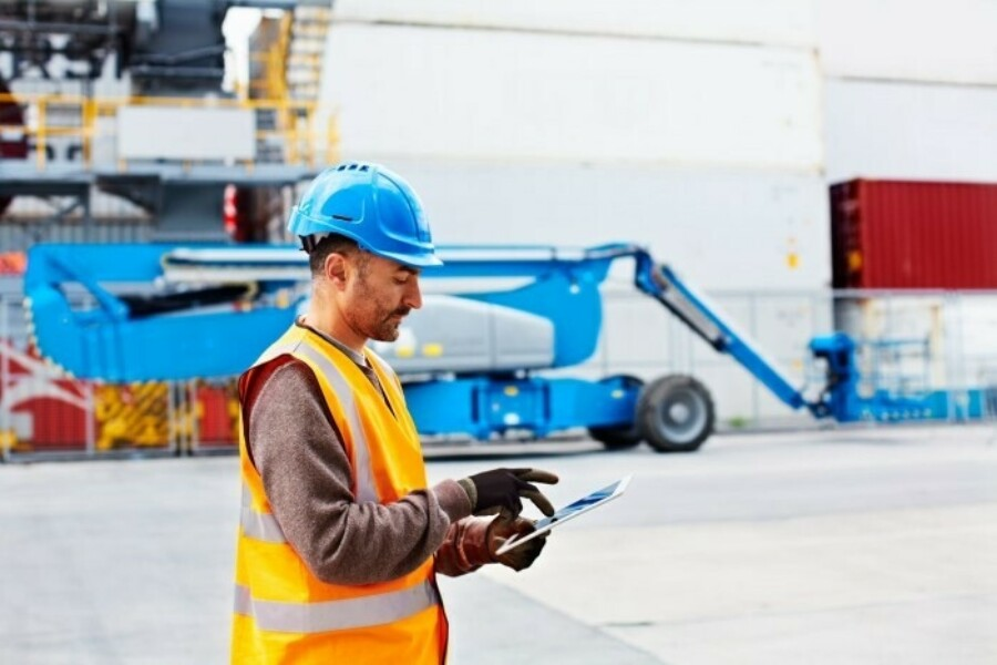 Man wearing hard hat in logistics yard using a tablet