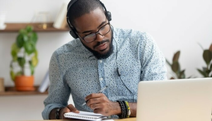 Man takes notes while listening to laptop with headphones