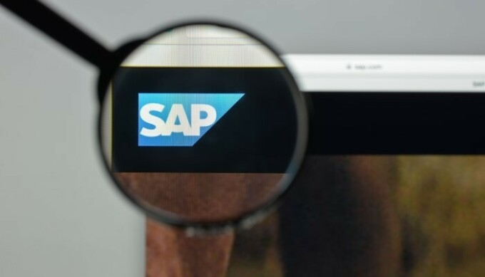 magnifying glass held over SAP logo on computer screen