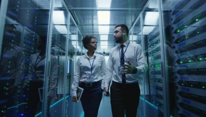 woman and man walking through a data center