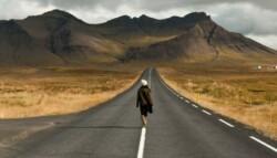individual walking forward on empty road toward mountains