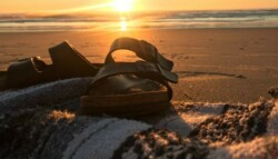 A pair of Birkenstock sandals placed on top of a blanket on the beach.
