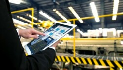 person in warehouse using tablet to track supply chain