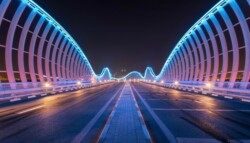 Modern bridge with neon beams lit up at night