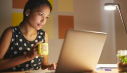 Woman holding coffee mug sitting in front of computer