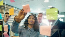 Group of co-workers sharing ideas with post-it notes
