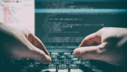Software developer programming code on a laptop.