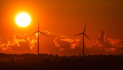 two power-generating windmills with sunset and clouds