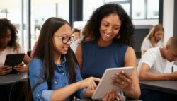 Female teacher mentoring younger students in a classroom