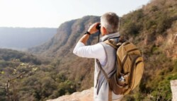 man on a mountain ledge looking at the distance with binoculars