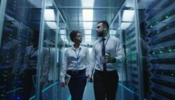 woman and man walking through a data center
