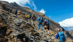 guide leading mountain climbers up a steep rocky summit