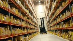 forklift driving down a warehouse aisle stocked with materials