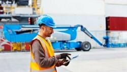 Man wearing hard hat in logistics yard using a tablet