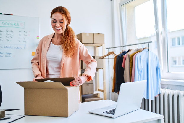A woman closes a box she was packing. In the background are more boxes, a whiteboard, and a rack of clothing.