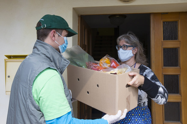 A man in a face mask and ball cap hands a box of groceries to a woman who also wears a face mask.