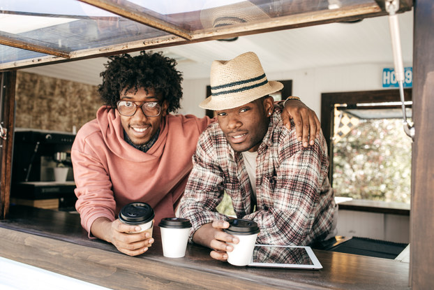Two men lean on the ledge of the window of a food truck. One man, wearing glasses and a coral sweater, has his army around the shoulders of the other man, who wears a plaid shirt and a fedora. In front of them on the window ledge are white coffee cups with black lids and an electronic tablet.