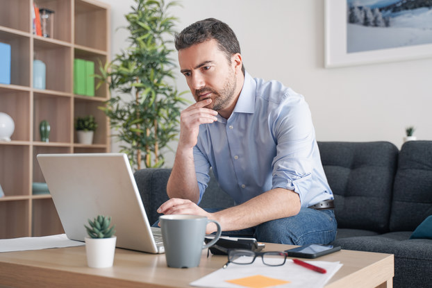 A man sits on a couch and considers his laptop with one hand on his chin in thought. The laptop sits on a coffee table in front of the man, along with glasses, a coffee mug, and a small potted succulent. In the background are a decorative bookshelf and a tall potted plant.