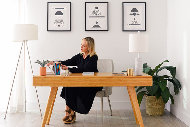 woman working at a fernish desk in home office