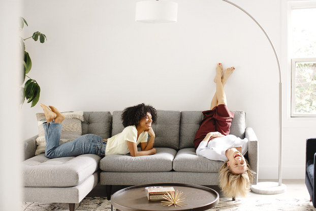 two women relaxing on a fernish couch