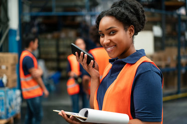 A woman in a dark blue polo shirt and neon orange vest holds her smart phone near her face with one hand and holds a clipboard with the other hand. In the background, employees dressed similarly to the woman are standing around a warehouse filled with cardboard boxes and packages of bottled water.