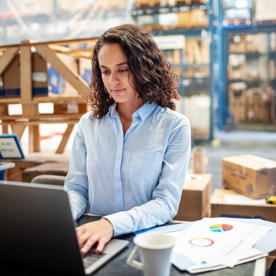 woman working on laptop in warehouse