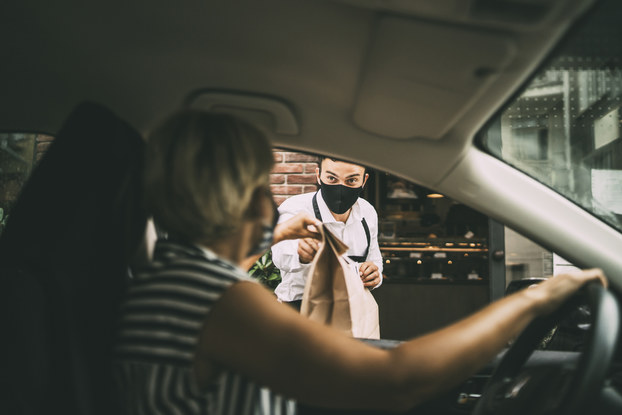 woman picking up curbside takeout from man at restaurant