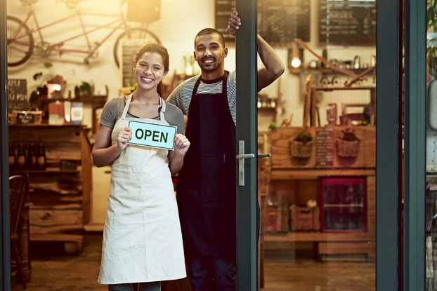 A man and a woman stand smiling in the doorway of a shop. The woman holds an OPEN sign.