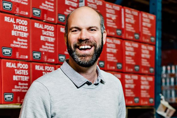 headshot of ian walker of hippie snacks in a warehouse