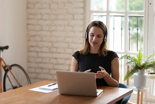woman working on laptop and using headset at kitchen table