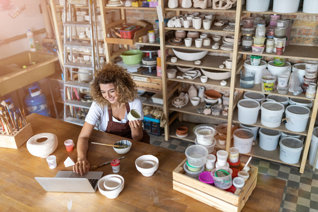 A woman works on her laptop at a large wooden table scattered with pottery. Behind her are shelves of handmade bowls, pots, buckets, and other pieces of pottery.