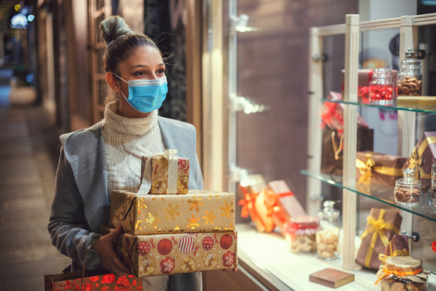 woman wearing mask holding wrapped holiday gifts
