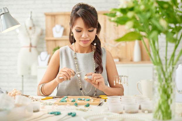 A woman uses pliers to adjust a piece of jewelry made out of a large pearl. Other stones, including bright green malachite, are scattered on the desk in front of her.