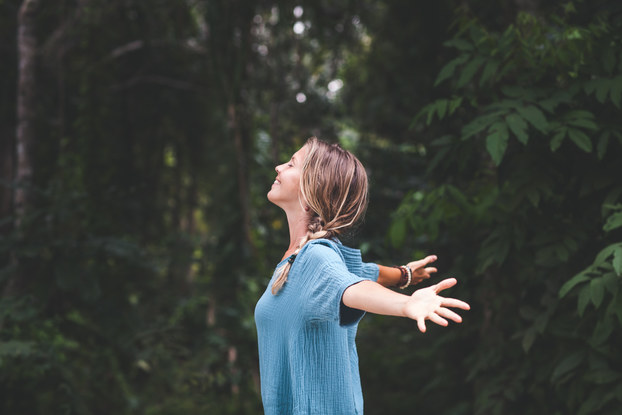 woman standing in nature with her head up and arms out