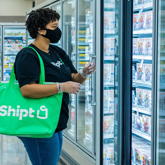 A Shipt employee wearing a mask looks through the frozen food section of a partnering grocery store for requested food items, which will be placed in the large green bag hanging from the shopper's shoulder.